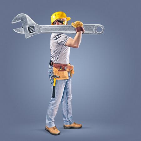 ツール ベルトそしてレンチで建設労働者 写真素材