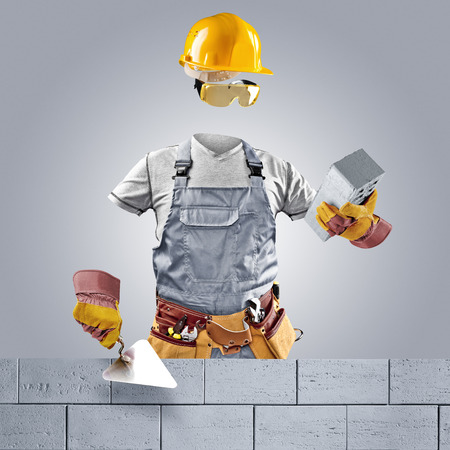invisible worker with trowel and brick wall