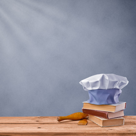 cap chef, cookbook and kitchenware on a grey vintage background photo