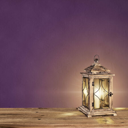 vintage lantern with a candle on a violet vintage background photo