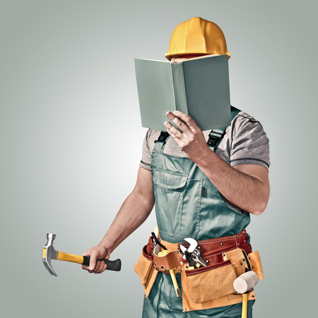 or instruction: construction worker with a tool belt and book Stock Photo