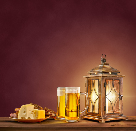 old lantern with beer, cheese and bread on vintage background photo