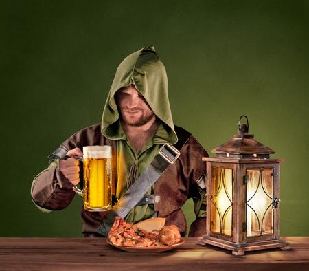 medievales: hombre medieval en una taberna con una cerveza en el fondo de la vendimia