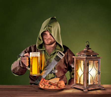 tavern: medieval man in a tavern with a beer on the vintage background