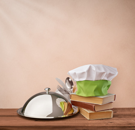 cloche: food tray, cap chef and cookbook on a beige vintage background