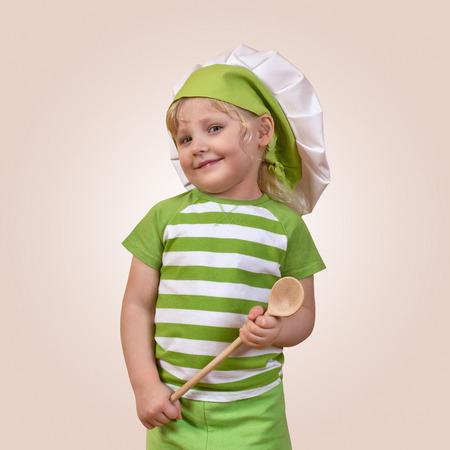 ベージュの背景の木のスプーンで笑顔の子シェフ