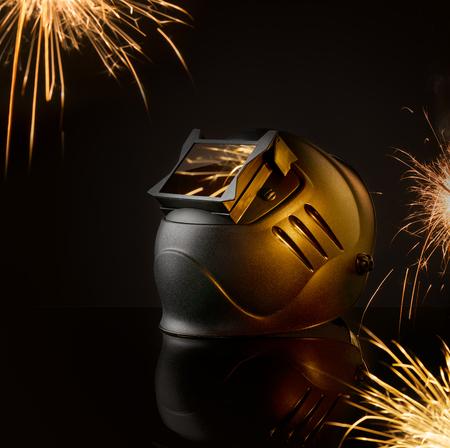 mask welder on the background of sparks from welding process Standard-Bild