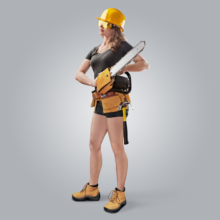 worker girl in a helmet with a chain saw on grey background photo