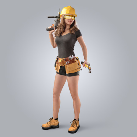 worker girl in a helmet with drill and hammer on grey background 스톡 콘텐츠
