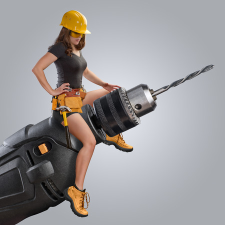 worker girl sitting on a drill on grey background