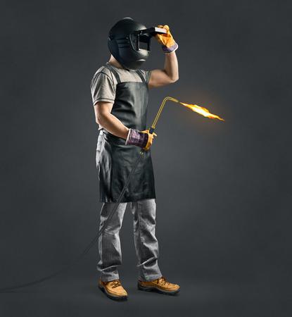 ouvrier soudeur avec la machine de soudage de gaz sur fond gris