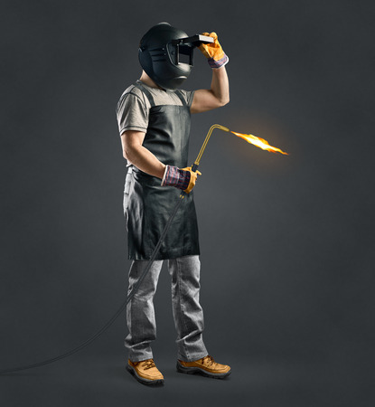 delantal: soldador trabajador con la m�quina de soldadura de gas sobre fondo gris Foto de archivo
