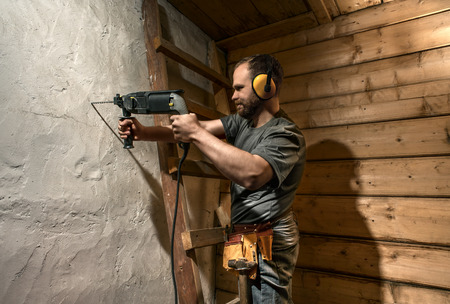 construction worker drill perforate concrete wall on wood background Standard-Bild