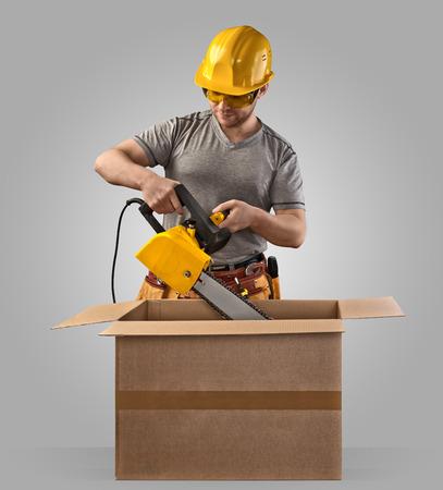 建設労働者配信チェーン鋸を持つボックスをアンパックします。 写真素材