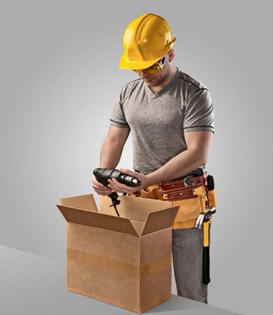 box construction: construction worker unpacks the box with delivery drill on gray background