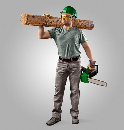 woodcutter in helmet with chain saw and log on  grey background