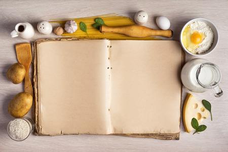 istruzione: libro di cucina d'epoca e gli ingredienti per la ricetta cibo intorno a una cornice sullo sfondo del tavolo