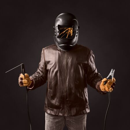mounter: welder in protective helmet with welding apparatus in the hands on brown background Stock Photo