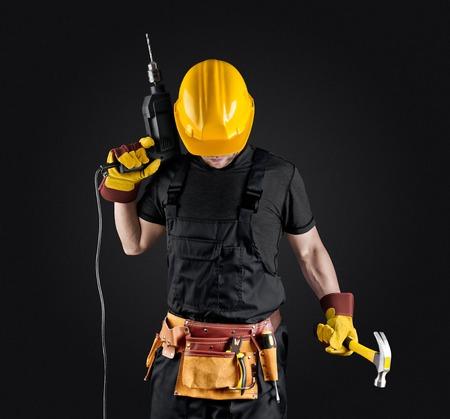 trabajador de la construcción en el casco con el martillo y el taladro en el fondo oscuro