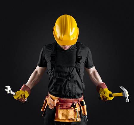 construction worker in helmet with hammer and wrench on dark background Stock Photo