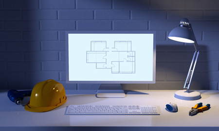 engineer computer: computer, table lamp, helmet and construction tools on a background of brick wall