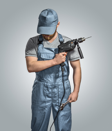 erector: construction worker builder with drill and wrench on the isolated background Stock Photo
