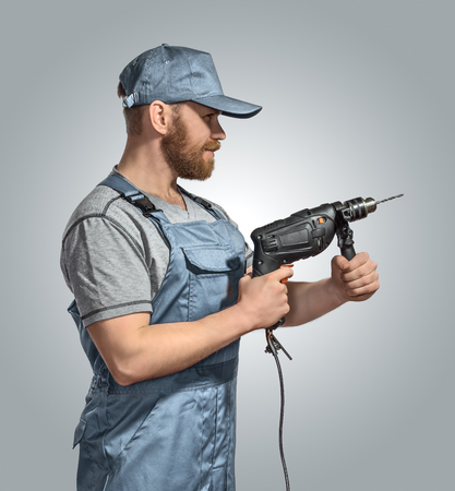 drill: construction worker builder with drill on the isolated background