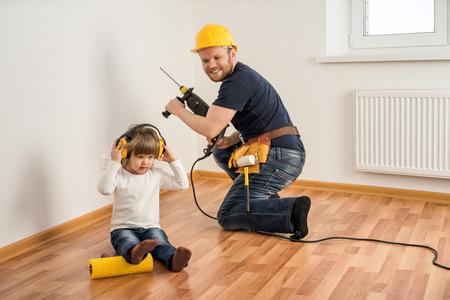 ドリルと小さな子供のヘルメットの建設労働者は家の修理をします。 写真素材