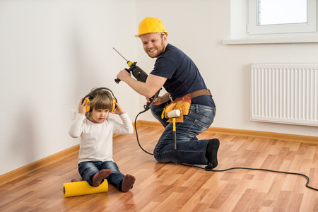 construction worker in helmet with a drill and a little child make repairs in the house