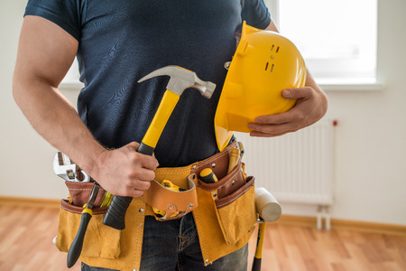 construction worker with tool belt, helmet and hammer Stock Photo