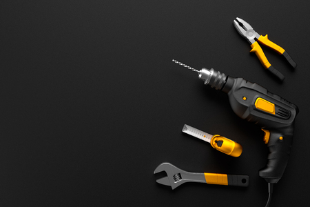 drill, wrench and other construction tools on the black background textures Standard-Bild
