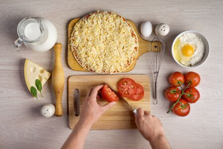 chef: hands chefs cut tomatoes, cooking pizza ingredients on wooden background texture Stock Photo