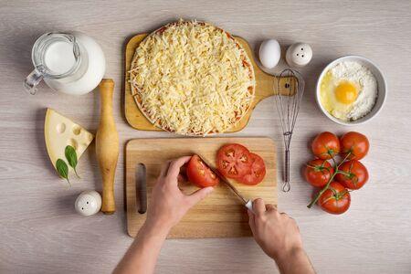 ręce kucharzy wyciąć pomidory, gotowania składników pizzy na drewnianym tle tekstury