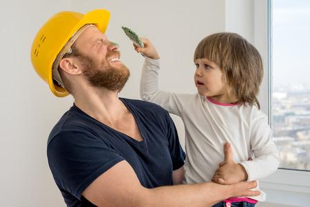 ouvrier: famille heureuse, travailleur de la construction dans un casque et un petit enfant avec un pinceau Banque d'images