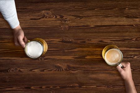古い木製のテクスチャの背景の手でビールのジョッキ