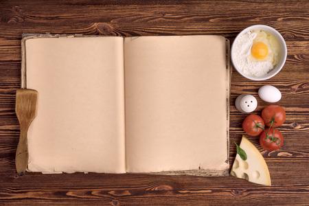 cocineros: libro de cocina de edad, los ingredientes para una comida en un fondo de madera de la vendimia Foto de archivo