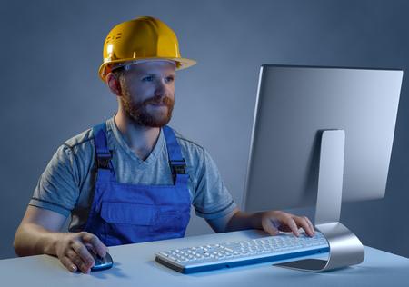 obrero trabajando: Constructor del trabajador en el casco y el uniforme que trabaja en un ordenador, se puede comprar en la tienda online
