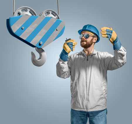 adjuster: worker builder in helmet manages the construction process, crane hook on the isolated background