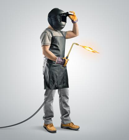 soldador: soldador trabajador en una m�scara protectora con la m�quina de soldadura de gas en el fondo aislado Foto de archivo