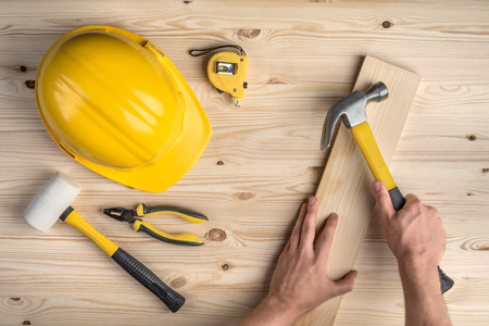 hammer: tools and hands working with hammer and helmet on wooden background