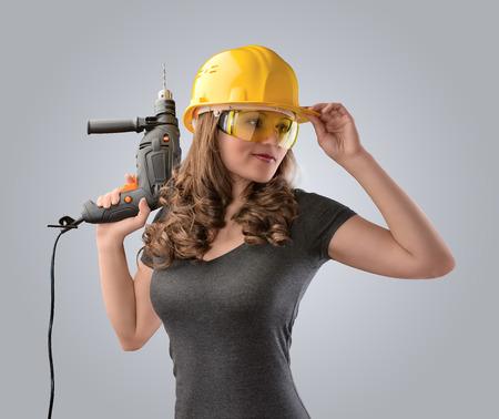 werknemer meisje in een helm met een boor op een grijze achtergrond Stockfoto