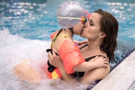 mama e hija: baño de la familia, el joven madre besa a su hija en la piscina