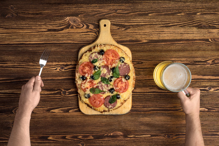 hands with pizza and beer on vintage wooden background
