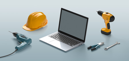 laptop, helmet, drill and construction tools on an isolated background