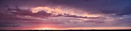 purple panorama of the sky at sunset with clouds and sun