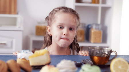 little girl looks at the sweets