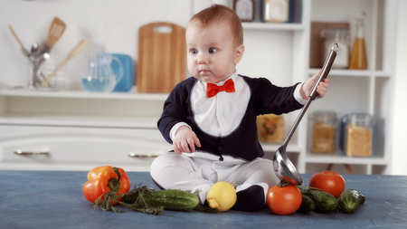 baby chef sitting with ladle and vegetables