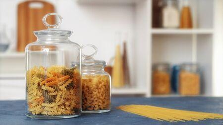 Pasta in glass jar on white background