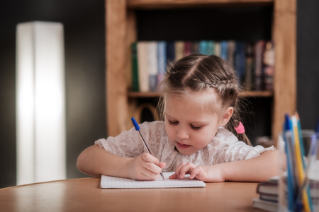 little girl draws, learns to write Stock Photo