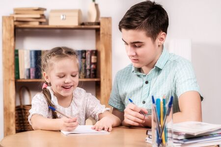 teenager and a little girl learning Stock Photo